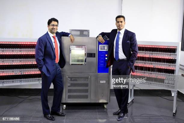 Sahir Berry chief executive officer of AfriOne Ltd right and Hemang Kapur director of AfriOne Ltd pose for a photograph beside machinery during the...