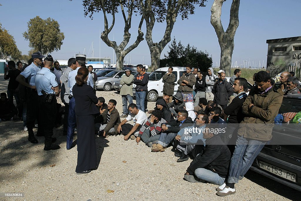 Sahrawi seasonal workers who came in the Bordeaux's region for the grape harvest speak with gendarmes, on October 5, 2012 in Pauillac, one day after being involved in a street fight with Moroccan born inhabitants. The fight started after 'a provocation nearby a praying area' and notably a 'T-shirt bearing a slogan for an independent Western Sahara' according to French gendarmerie.