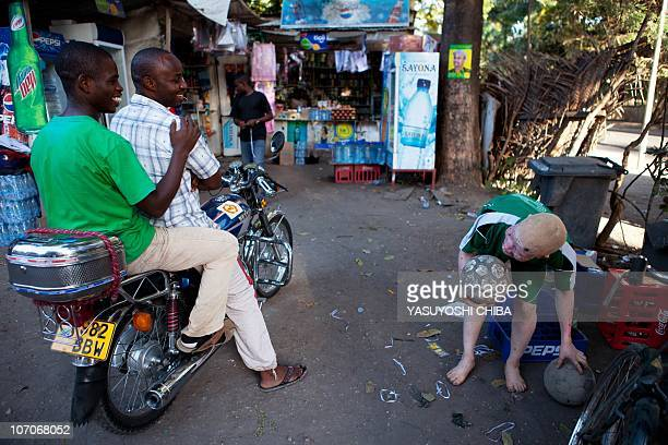 Said Seremani jokes with two men riding a motorcycle past a kiosk where Seremani leaves his team's balls overnight with the owner of the store near...