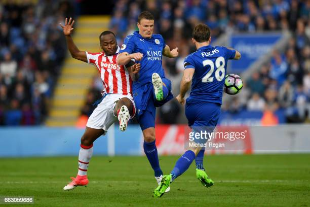 Saido Berahino of Stoke City and Robert Huth of Leicester City battle for possession during the Premier League match between Leicester City and Stoke...