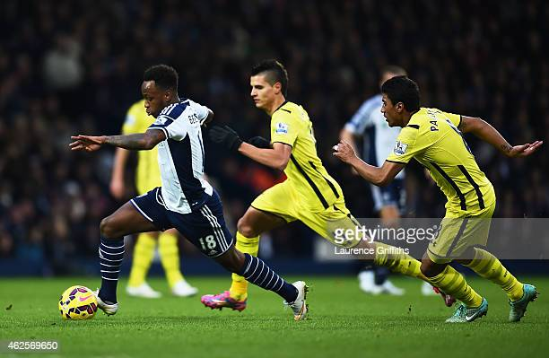 Saido Berahino of West Brom goes past Erik Lamela and Paulinho of Spurs during the Barclays Premier League match between West Bromwich Albion and...