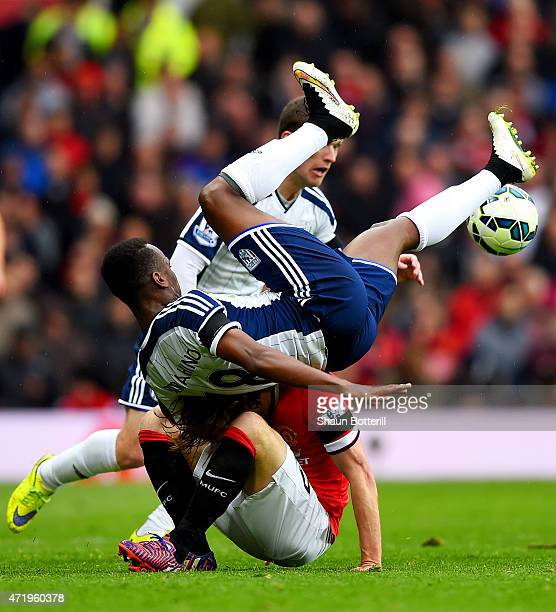 Saido Berahino of West Brom lands on Daley Blind of Manchester United as they battle for the ball during the Barclays Premier League match between...