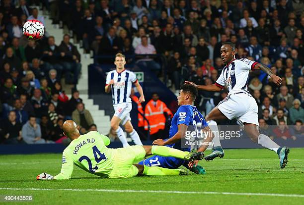 Saido Berahino of West Bromwich Albion beats goalkeeper Tim Howard and Tyias Browning of Everton to score their first goal during the Barclays...