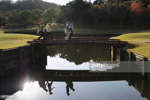 Saiki Fujita and Mayumi Shimomura of Japan walk over a bridge on the 2nd hole during the first round of the Itoen Ladies Golf Tournament 2017 at the...