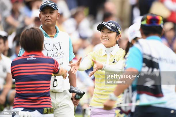 Saiki Fujita of Japan shakes hands Hiroko Azuma of Japan after her putt on the 18th green during the final round of the CAT Ladies Golf Tournament...
