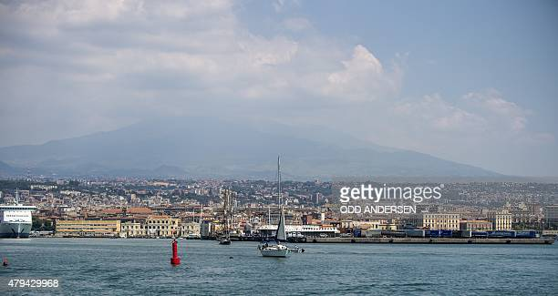 A sail boat is seen leaving the harbour in Catania with Mount Etna rising into the cloud behind on July 4 2015 AFP PHOTO / ODD ANDERSEN