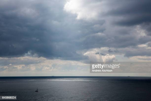 A sail boat sails across the tranquil waters of The English Chanel in the forefront and two large shipping containers sail along the horizon line as...