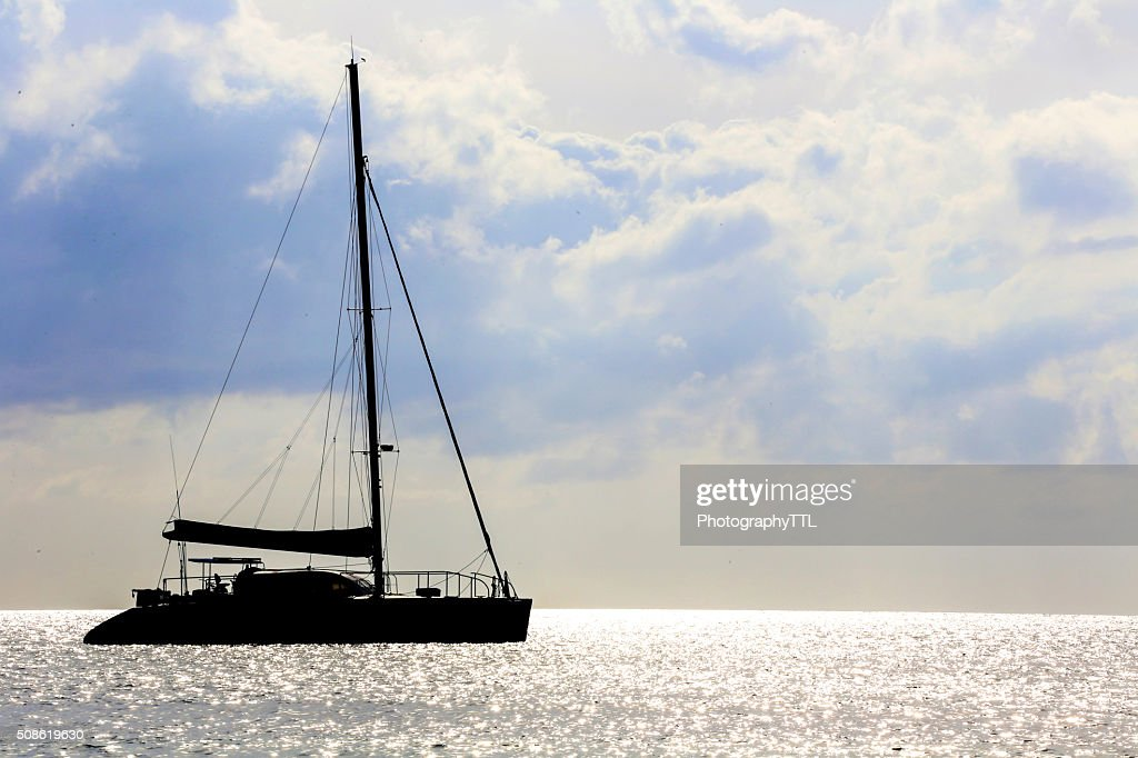 Sail boat silhouette in a sea at sunset : Stock Photo