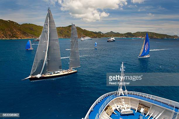 Sail boats cross the bow of a cruise ship off the island off Saint Barthélemy in the Leeward Islands