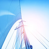 Closeup photo of sail on blue sky backdrop, bright sun light, detail of water transport, yachting sport, sailboat on the sea, summer vacation concept