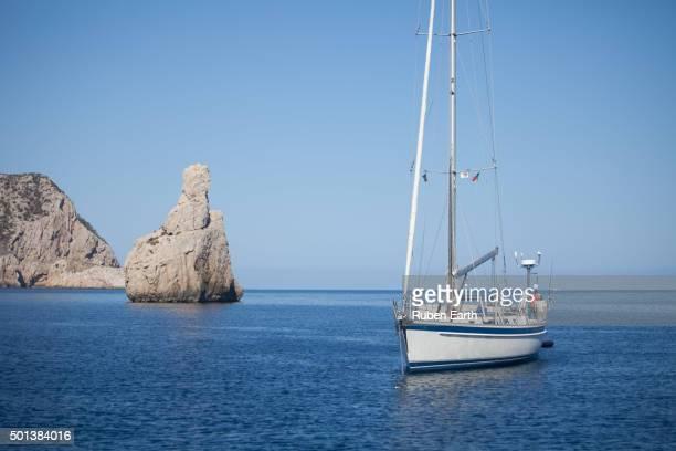 Sailboat anchored in Ibiza near Benirras beach in day time