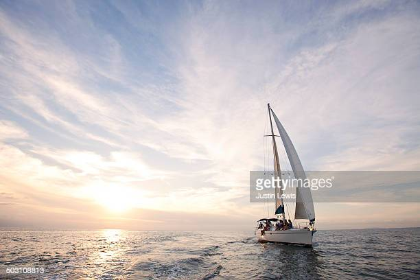 Sailboat cruise during gorgeous sunset at sea