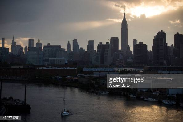 A sailboat floats down Newtown Creek which lets out into the East River with the Empire State Building and Manhattan skyline in the background on May...