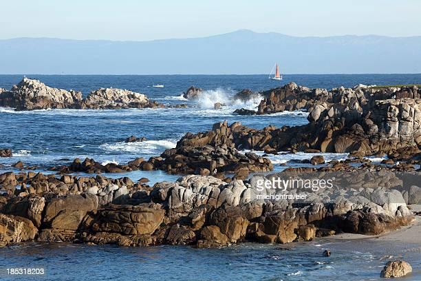 Sailboat in Monterey Bay along rocky coast California