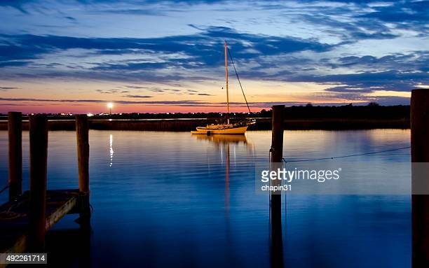 Sailboat in Shimmering Water at Dusk