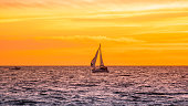 Sailboat in the ocean during sunset