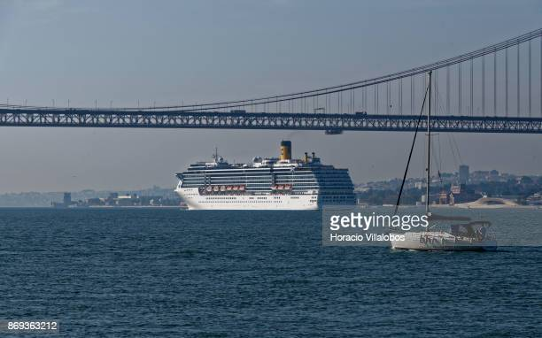 A sailboat is seen while cruise ship Costa Mediterranea sails the Tagus River by the 25 de Abril bridge on October 31 2017 in Lisbon Portugal...