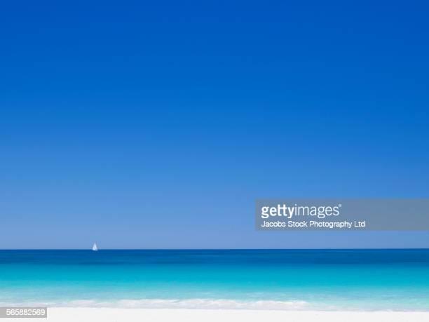 Sailboat on ocean horizon near beach