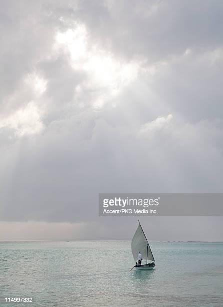 Sailboat passes through tropical sea below storm