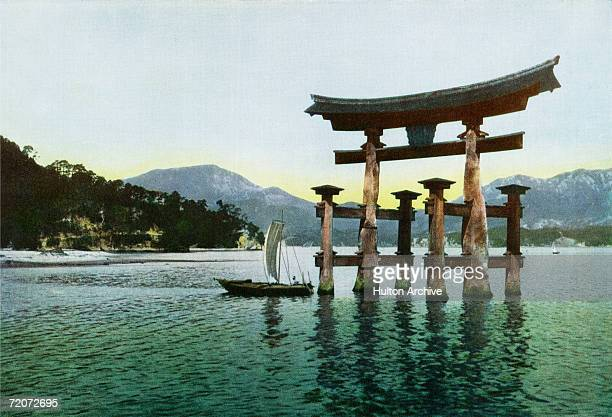 A sailboat passing the torii of Itsukushima Shrine off Itsukushima Island Japan circa 1930