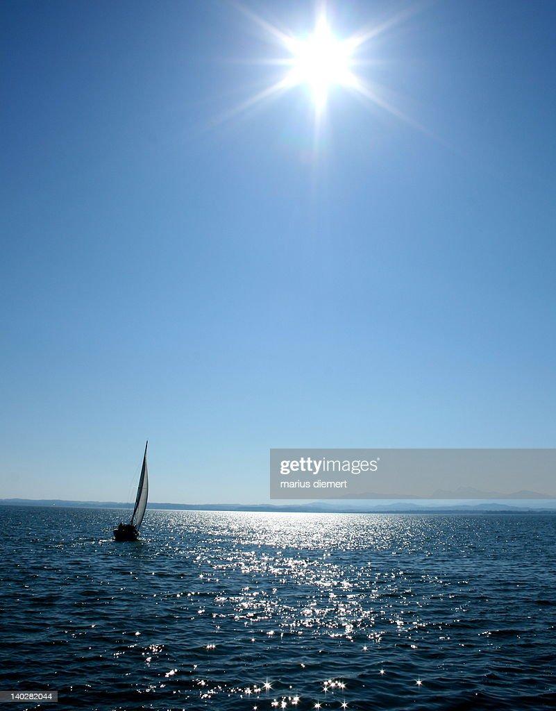 Sailboat sailing on open sea against blue sky : Stock Photo