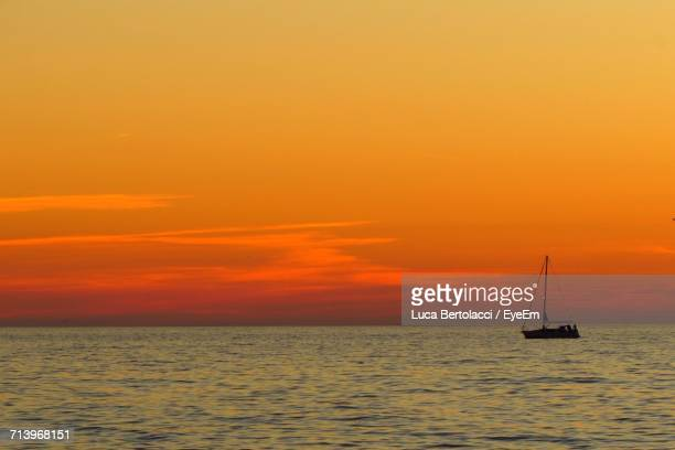 Sailboat Sailing On Sea Against Romantic Sky At Sunset