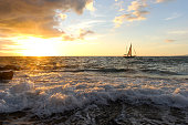 Sailboat Sunset is a sailboat with people aboard close to shore with a rough wave rolling in and the sun setting on the ocean horizon.