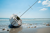sailboat wrecked and stranded on beach