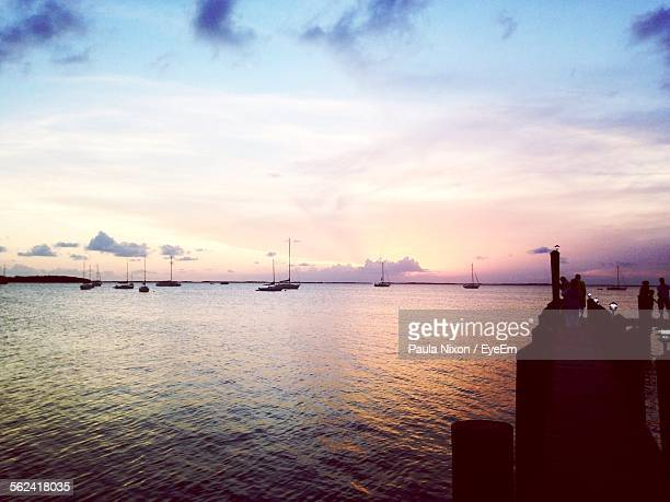Sailboats And Silhouettes Of People By Lake At Sunset