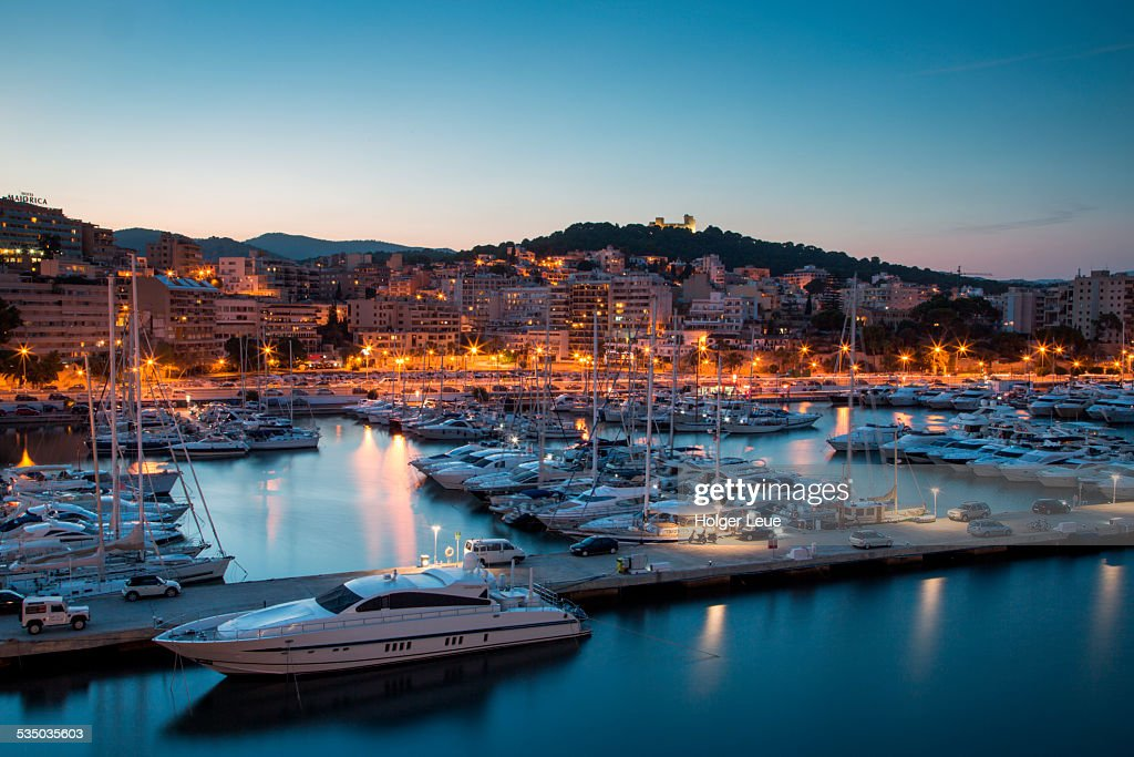Sailboats in marina and Castell de Bellver at dusk