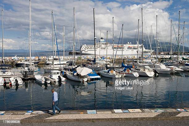 Sailboats in marina and cruise ship at pier
