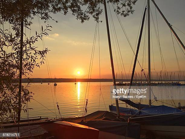 Sailboats Moored By Ammersee Lake Against Sky During Sunset