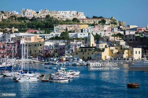 Sailboats Moored In Sea Against Cityscape