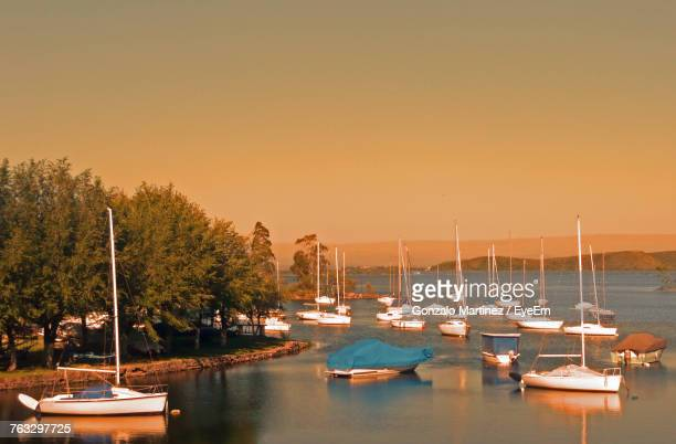 Sailboats Moored On Harbor Against Clear Sky During Sunset