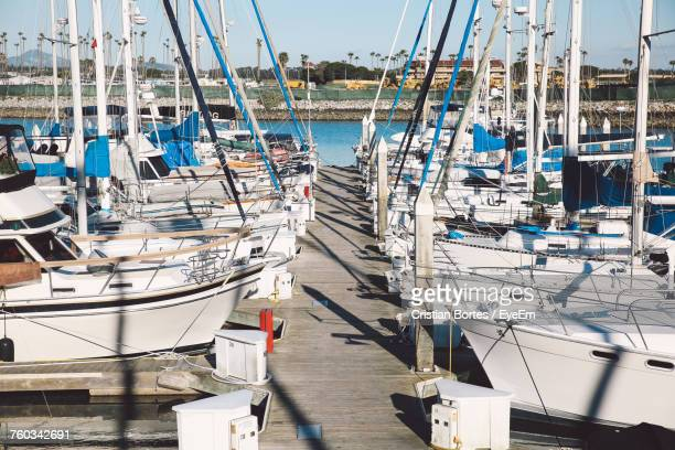 Sailboats Moored On Harbor Against Clear Sky