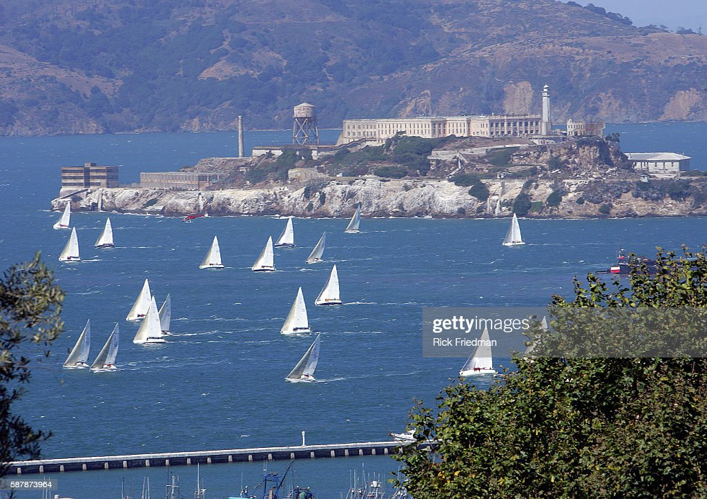 Sailboats sail past Alcatraz prison on Alcatraz Island in San Frnacisco Bay