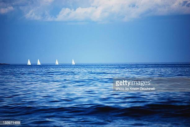 Sailboats sailing on horizon line
