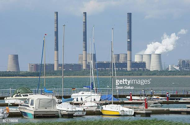 Sailboats stand docked at Baerwalde Lake as the Boxberg coalfired power plant is visible behind on August 4 2008 at Uhyst Germany The local coal...