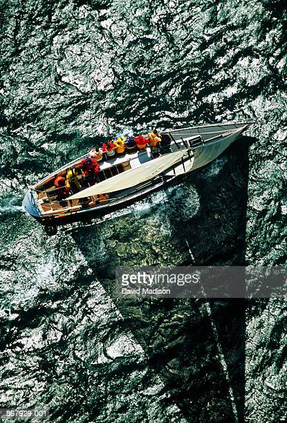 Sailing boat casting shadow on sea, overhead view