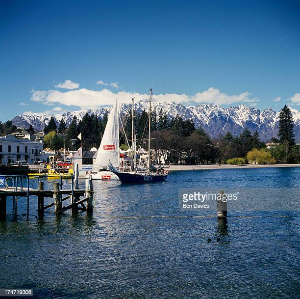 A sailing boat on beautiful Lake Wakatipu framed by snowy mountain peaks and fjords at Queenstown on New Zealand's South Island A major tourist...