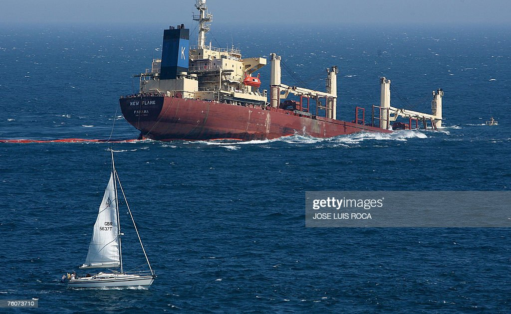 A sailing boat passes near the sinking cargo ship 'New Flame' registered in Panama after it collided yesterday with an oil tanker in the Strait of...