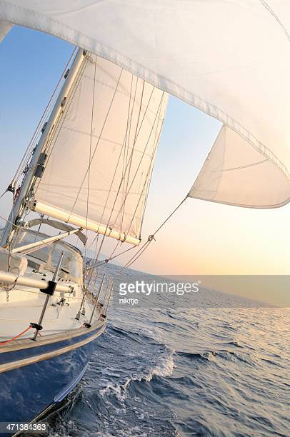 Sailing boat under sails in the evening