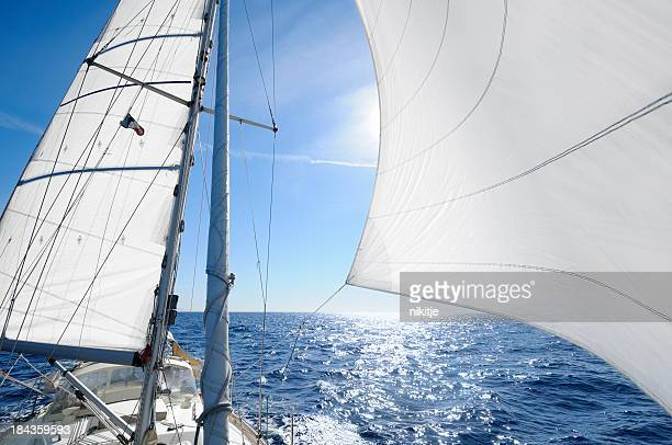 Sailing boat with the sun shingn behing sail