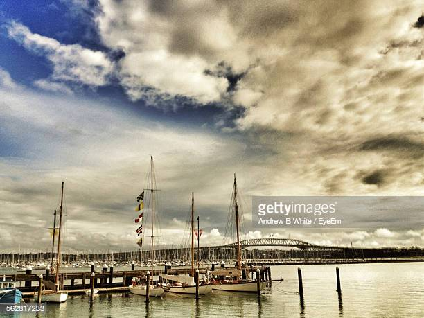 Sailing Boats Moored In Harbor In Front Of Auckland Harbor Bridge Against Cloudy Sky