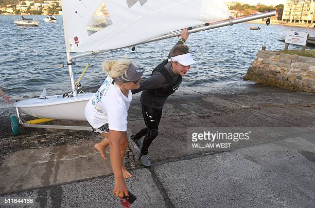 Sailing coach Alex South helps 15yearold sailor Jack Littlechild pull his dinghy out of the water after a training run on Sydney Harbour on February...