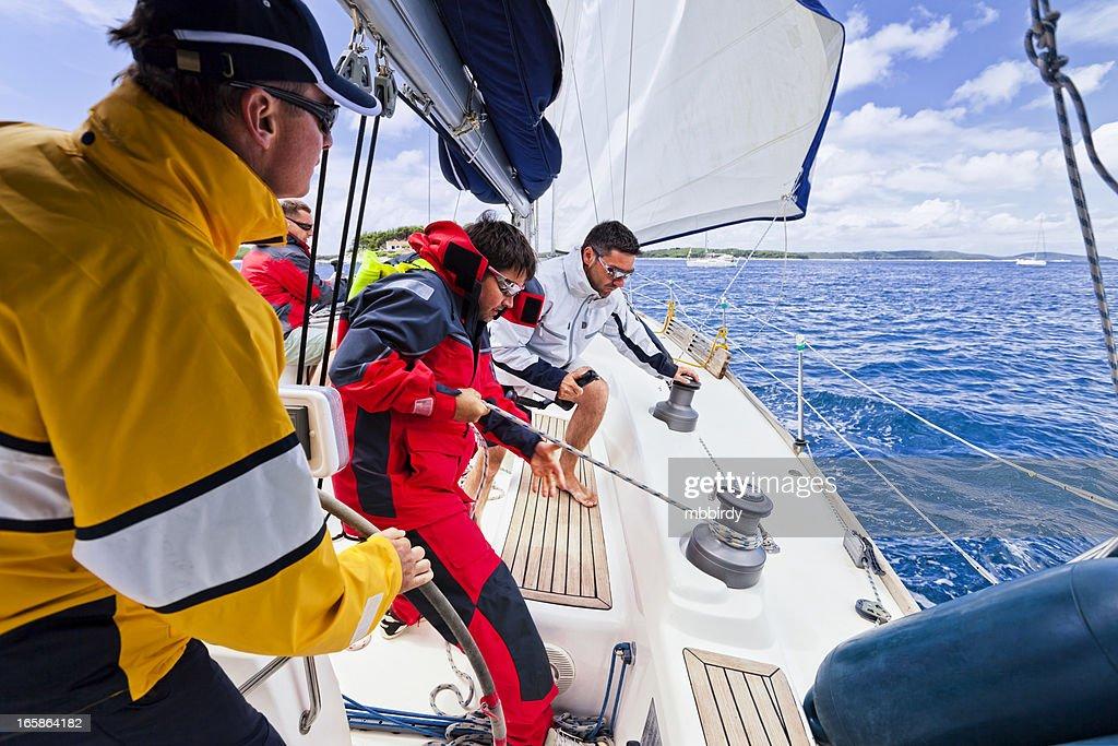 Sailing crew beating to windward on sailboat