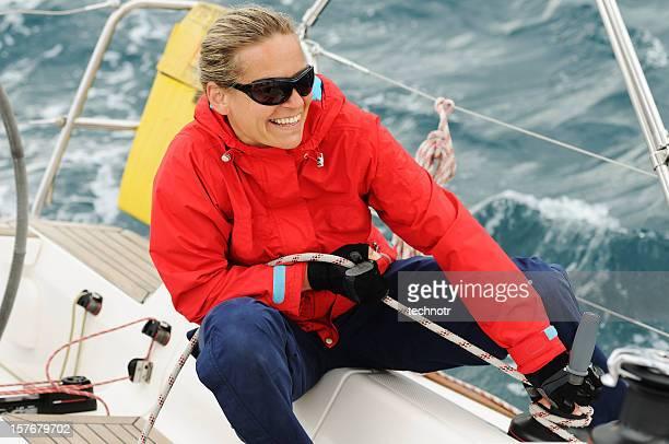 Sailing crew member on sailboat trimming front sail