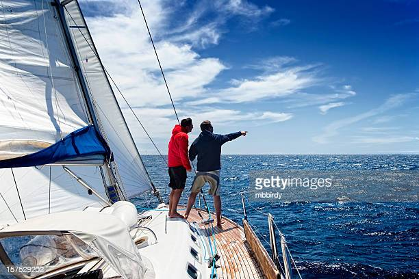 Sailing crew on sailboat observing the sea