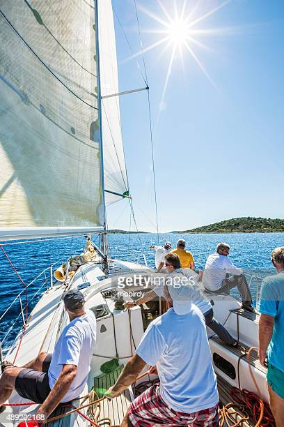 Sailing crew on sailboat on regatta, vertical