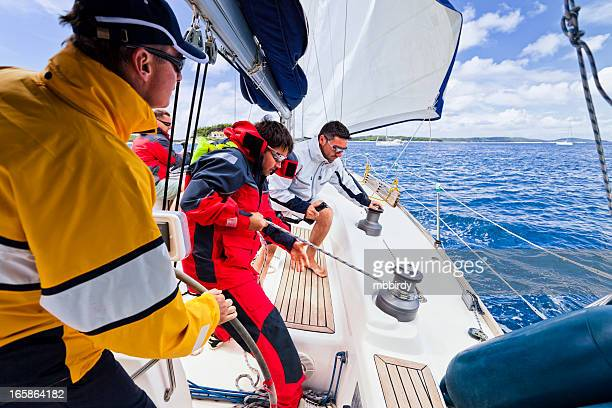 Sailing crew tacking a sailboat
